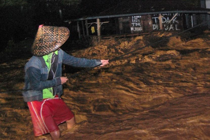 Seorang warga berpegangan pada sebuah tali saat banjir bandang, di Kelurahan Limaumanis, Kecamatan Pauh, Padang, Sumbar, beberapa waktu lalu