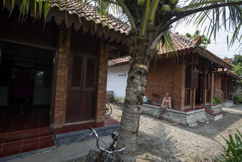 Seorang warga duduk di pelataran rumah bergaya arsitektur Majapahit di Desa Bejijong, Kawasan Cagar Budaya Nasional Trowulan, Mojokerto, Jawa Timur, Kamis (10/3).