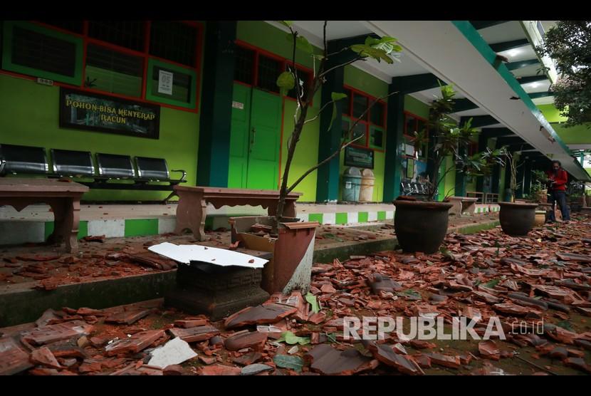 Seorang warga melintas di depan bangunan sekolah yang rusak akibat gempa di SMK Negeri 1 Turen, Malang, Jawa Timur, Sabtu (10/4/2021). Gempa yang mengguncang kawasan Malang dan sekitarnya membuat sejumlah bangunan rusak.