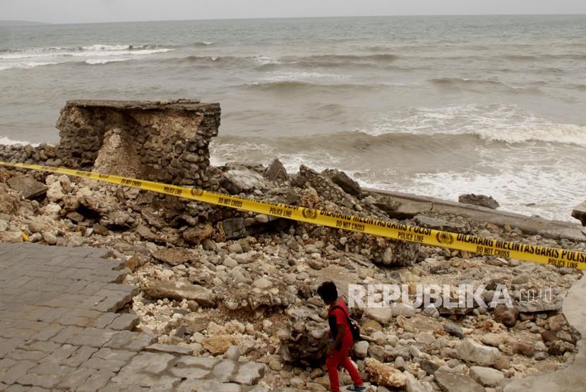 Seorang warga melintas di dermaga tempat wisata kuliner yang rusak akibat diterjang gelombang tinggi di pesisir pantai Kota Kupang, NTT beberapa waktu lalu