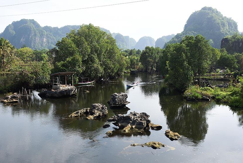 Seorang warga melintas di sungai Kampung Wisata Rammang-Rammang, Maros, Sulawesi Selatan. Pemerintah tengah mengusulkan kawasan ini menjadi Geopark Maros-Pangkep sebagai UNESCO Global Geopark  (ilustrasi)