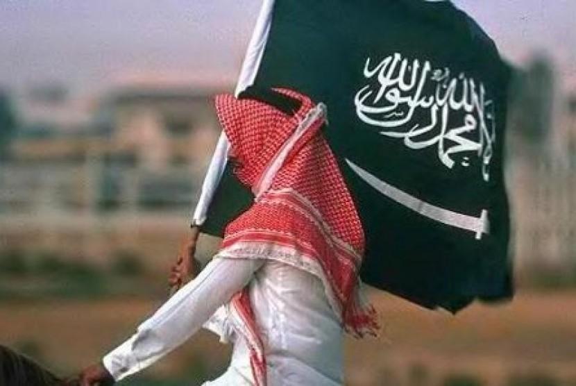 Seorang warga membawa bendera Arab Saudi (Ilustrasi).