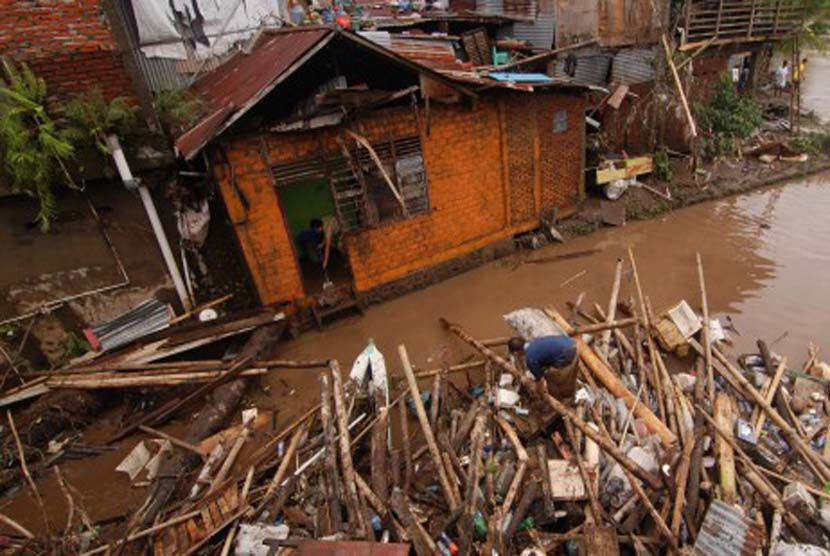 Seorang warga membersihkan lumpur rumahnya setelah terendam banjir. Bupati minta warga jangan lakukan penggalangan dana dengan meminta di jalan. Ilustrasi.