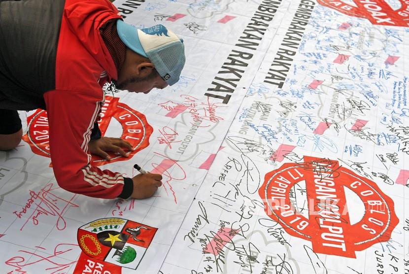 Seorang warga membubuhkan tanda tangan untuk mendukung Pemilu 2019 anti hoax saat berlangsung Hari Bebas Kendaraan Bermotor (HBKB) di Kawasan Bundaran HI Jakarta, Ahad (10/2/2019).