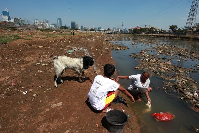 Seorang warga mencuci daging dialiran sungai Ciliwung yang mengering akibat kemarau di Jakarta, Senin (3/8).