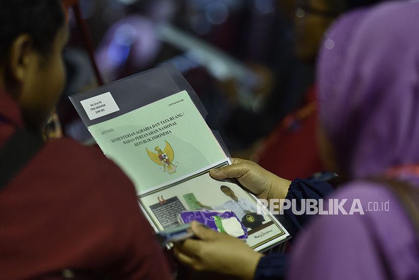 Seorang warga mengamati sertifikat tanahnya yang baru diterimanya di Sukabumi, Jawa Barat, Sabtu (7/4).
