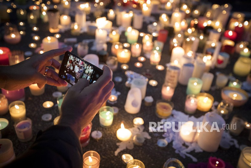 Seorang warga mengambil gambar lilin untuk mengenang korban penembakan di luar Masjid Al Noor di Christchurch, Selandia Baru, Senin (18/3/2019).