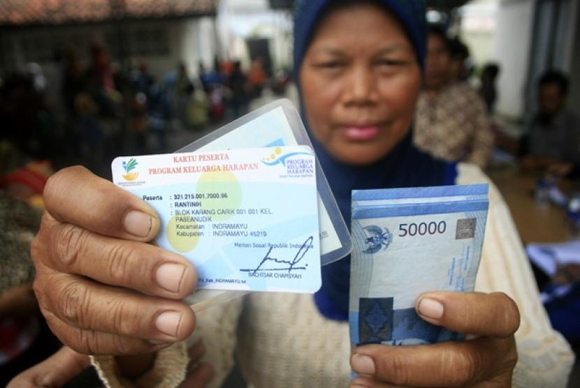 Seorang warga menunjukan kartu dan uang usai mengantre pembagian dana program keluarga harapan (PKH). ilustrasi