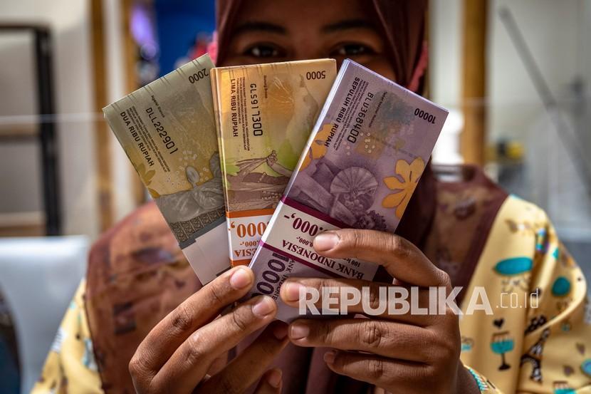 Seorang warga menunjukkan pecahan uang baru seusai menukarkan uangnya di tempat pelayanan penukaran uang Bank Indonesia (BI).