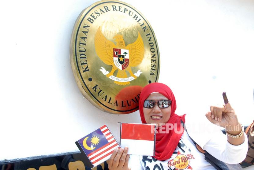 Seorang warga negara Indonesia menunjukkan jari yang telah dicelup tinta usai mencoblos di KBRI, Kuala Lumpur, Malaysia, Minggu (14/4/19).