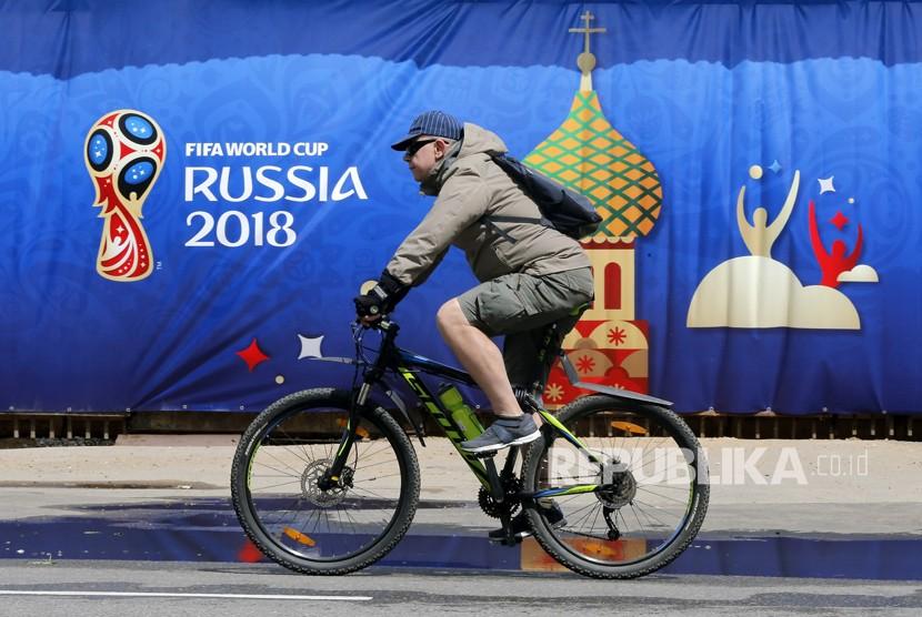 Seorang warga Rusia mengendarai sepeda di depan logo Piala Dunia 2018 di Moskow, Rusia, Rabu  (6/6).Piala Dunia 2018 akan berlangsung di Rusia dari 14 Juni hingga 15 Juli 2018.