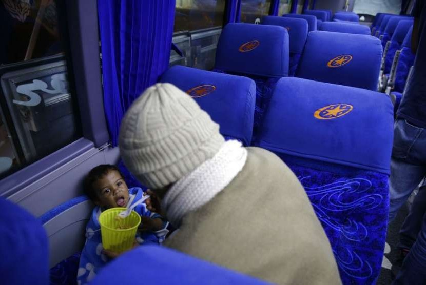 Seorang warga Venezuela menyuapi anaknya di dalam bus yang membawa mereka menuju Peru pada Jumat (24/8) waktu setempat. Ribuan orang telah menyeberang ke Peru beberapa jam sebelum pihak berwenang mulai menegakkan aturan baru.