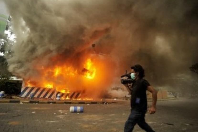 Seorang wartawan melintas di dekat pos polisi yang dibakar demonstran saat aksi unjuk rasa menolak kenaikan harga bahan bakar minyak (BBM).  (ilustrasi)