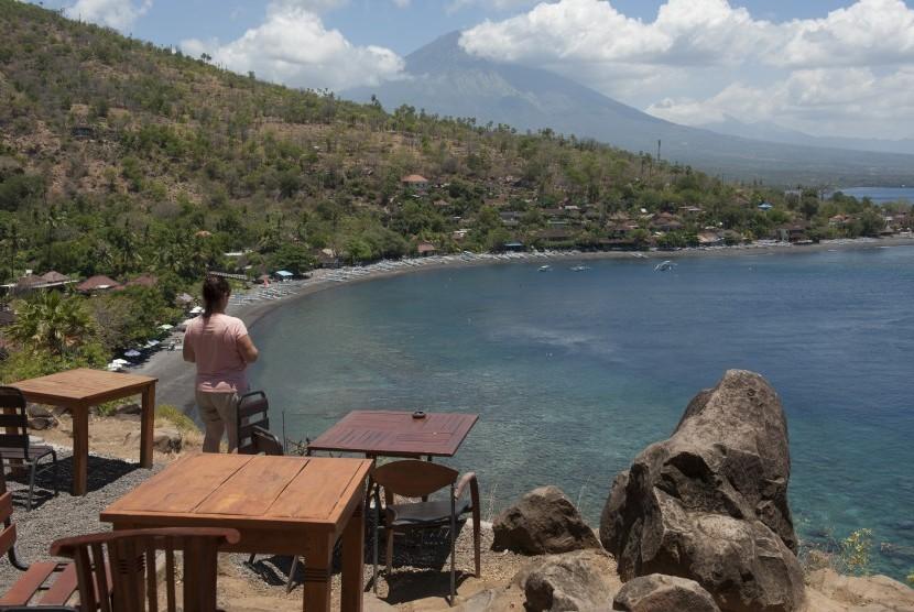 Seorang wisatawan menikmati pemandangan di Pantai Desa Amed, Karangasem, Bali, Jumat (29/9).