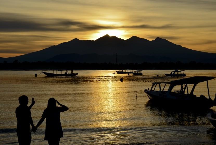 Sepasang wisatawan memperhatikan siluet Gunung Rinjani saat Sunrise (matahari terbit) di pinggiran pantai Gili Trawangan, Desa Gili Indah, Kecamatan Pemenang, Tanjung, Lombok Utara, NTB, Jumat (24/2).
