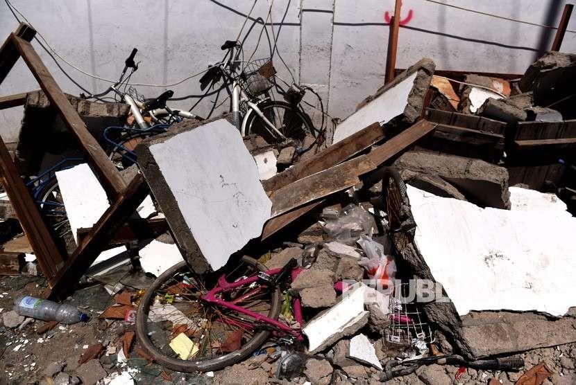 Sepeda tertimpa reruntuhan bangunan akibat gempa bumi di Gili Trawangan, Lombok Utara, NTB, Kamis (9/8).