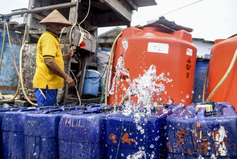 Serang pekerja mengisi air bersih ke dalam jerigen untuk dijual di Muara Angke, Jakarta, Senin (28/1/2019).