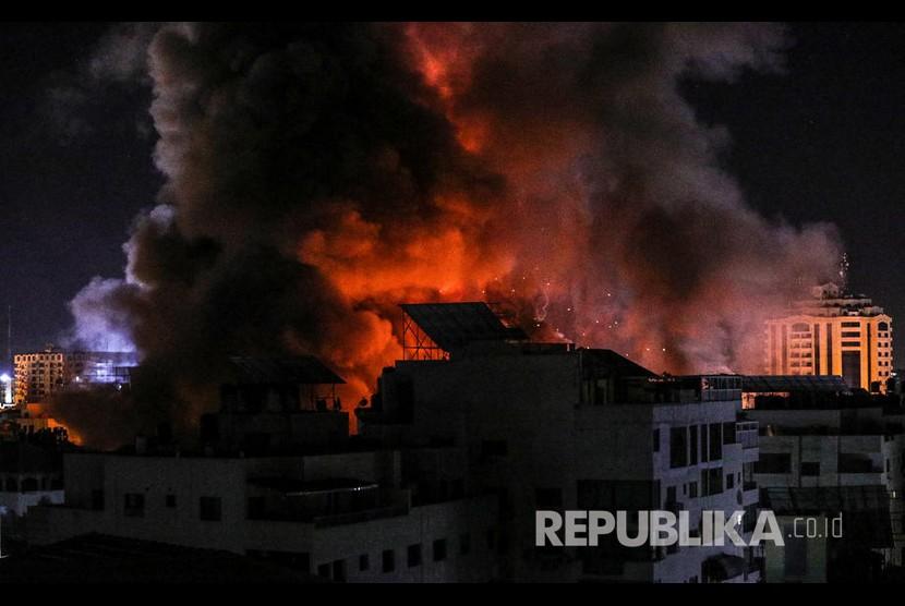 Asap dan api membumbung dari gedung yang menjadi target pemboman saat serangan udara Israel ke kota Gaza, Selasa (18/5).
