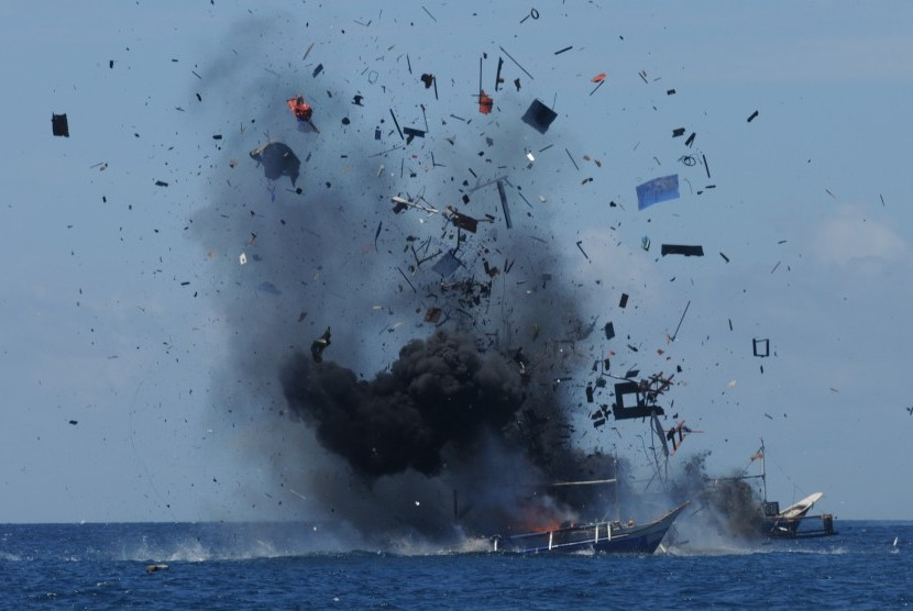 Serpihan dan asap keluar dari lambung kapal nelayan asing pelaku ilegal fishing yang ditenggelamkan di perairan Bitung, Sulawesi Utara, Rabu (20/5).  (Antara/Fiqman Sunandar)