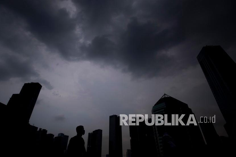 Siluet petugas keamanan berdiri saat awan mendung menghiasi langit Jakarta, Rabu (21/10/2020). BMKG menyatakan saat ini tengah terjadi fenomena La Nina di Samudera Pasifik yang bisa menimbulkan kondisi cuaca ekstrem di Indonesia, BMKG pun menghimbau masyarakat untuk tetap waspada dan berhati-hatI terhadap dampak yang dapat ditimbulkan dari fenomena alam itu.