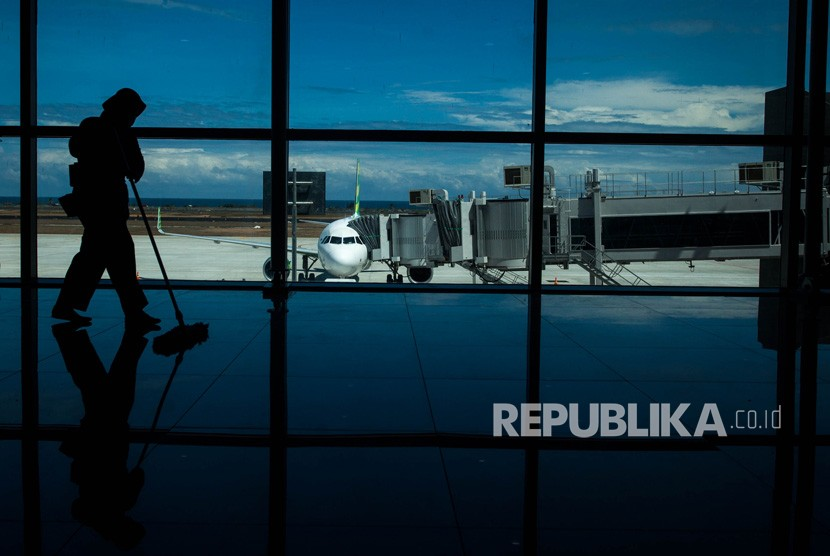 Siluet petugas kebersihan bekerja dengan latar belakang pesawat komersial maskapai Citilink terparkir di Yogyakarta International Airport (YIA) saat Proving Flight di Kulon Progo, DI Yogyakarta, Kamis (2/5/2019).