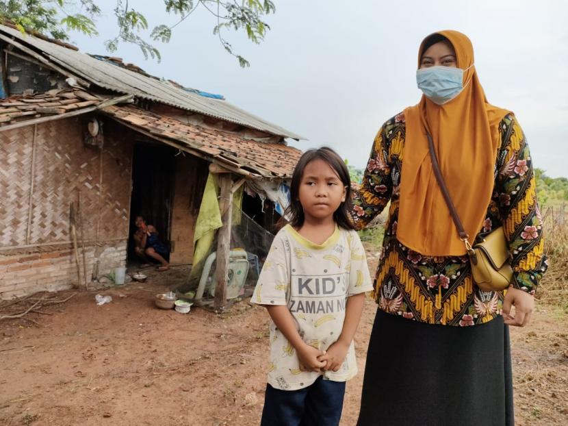 Sinta Murni didampingi petugas berdiri di depan rumahnya di Desa/Kecamatan Kroya, Kabupaten Indramayu, Rabu (23/6). Di usinya yang diperkirakan baru tujuh tahun, bocah itu seorang diri mengurus ibunya yang mengalami kondisi agak depresi.