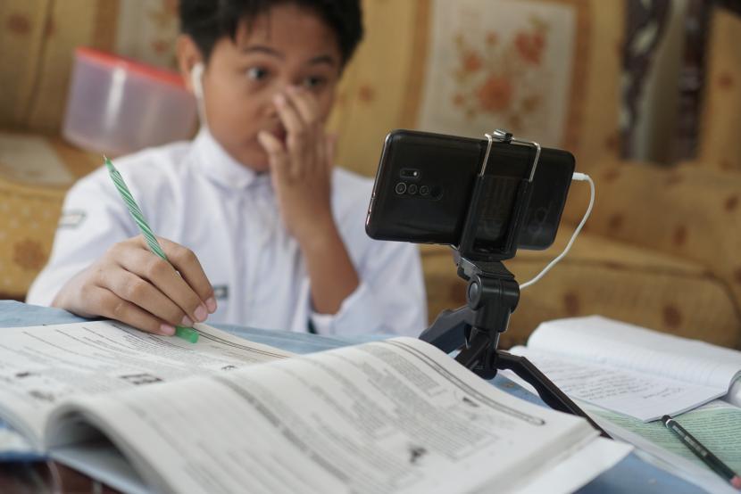 Siswa baru SMP Negeri II Surakarta mengikuti kegiatan belajar mengajar hari pertama masuk sekolah secara daring dari rumah di Kerten, Solo, Jawa Tengah, Senin (12/7/2021). Hari pertama masuk sekolah di Kota Solo masih dilakukan secara daring setelah sebelumnya Pemkot Solo menunda pembelajaran tatap muka (PTM) dilaksanakan pada bulan Juli akibat meningkatnya kasus COVID-19.