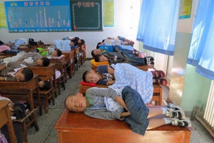 Siswa di Cina sedang tidur siang di atas meja belajar.