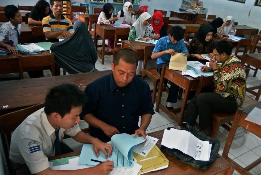 Siswa dibantu orang tuanya mengisi formulir daftar ulang pendaftaran peserta didik baru (PPDB) di SMA Negeri 3 Semarang, Jawa Tengah, Kamis (12/7).