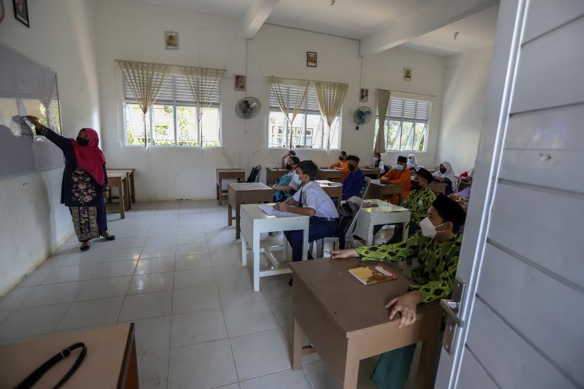 Siswa kelas tujuh mengikuti kegiatan pembelajaran tatap muka (PTM) hari pertama di SMPN 6 Batam, Kepulauan Riau, Selasa (21/9/2021). Kasus Covid-19 merebak menjadi klaster di 1.296 sekolah di seluruh Indonesia.