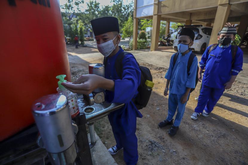 Siswa mencuci tangan saat akan memasuki area sekolah di SMPN 6 Batam, Kepulauan Riau, Selasa (21/9/2021). Sejumlah sekolah di Kota Batam yang telah mendapatkan izin dari Dinas Pendidikan Kota Batam mulai melakukan PTM dengan tetap menerapkan protokol kesehatan ketat.