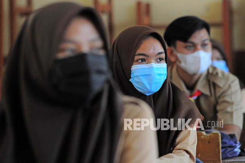 Siswa mendengarkan materi pelajaran sambil mengenakan masker saat hari pertama dimulainya kembali belajar tatap muka. ilustrasi