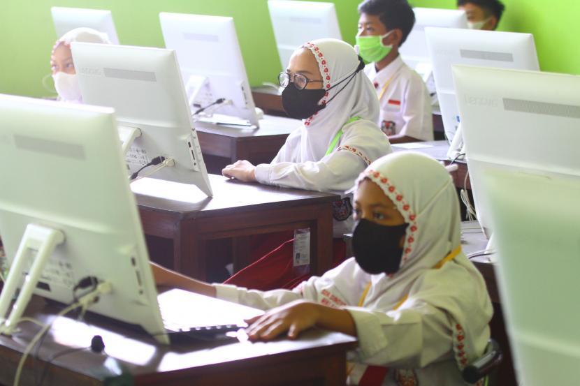 Siswa mengerjakan soal PPKn melalui komputer dalam Ujian Sekolah yang diadakan secara tatap muka di SDN Dinoyo 1 Malang, Jawa Timur, Senin (26/4/2021). Ujian sekolah sebagai salah satu syarat kelulusan tersebut diadakan serentak secara tatap muka di 250 sekolah dasar negeri maupun swasta di Kota Malang.