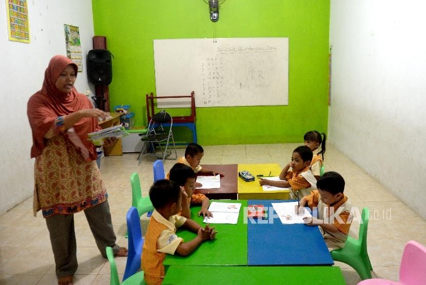Siswa Pendidikan Anak Usia Dini (PAUD) Seruni Indah belajar di bangunan majelis taklim swadaya masyarakat, Kalijodo, Jakarta, Selasa (16/2).