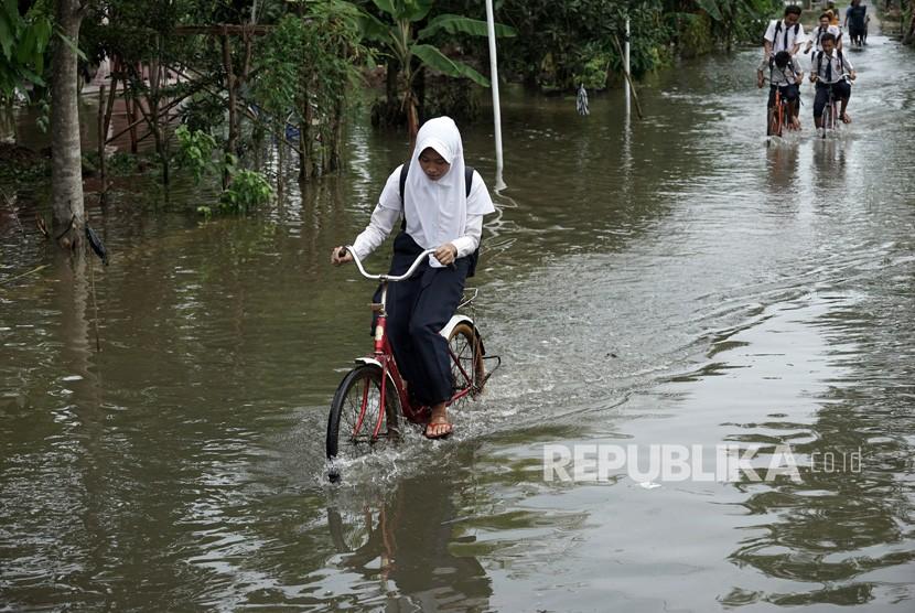 Siswa sekolah melintasi genangan air akibat banjir di Desa Kedungbenda, Nusawungu, Cilacap, Jateng, Selasa (13/11/2018).