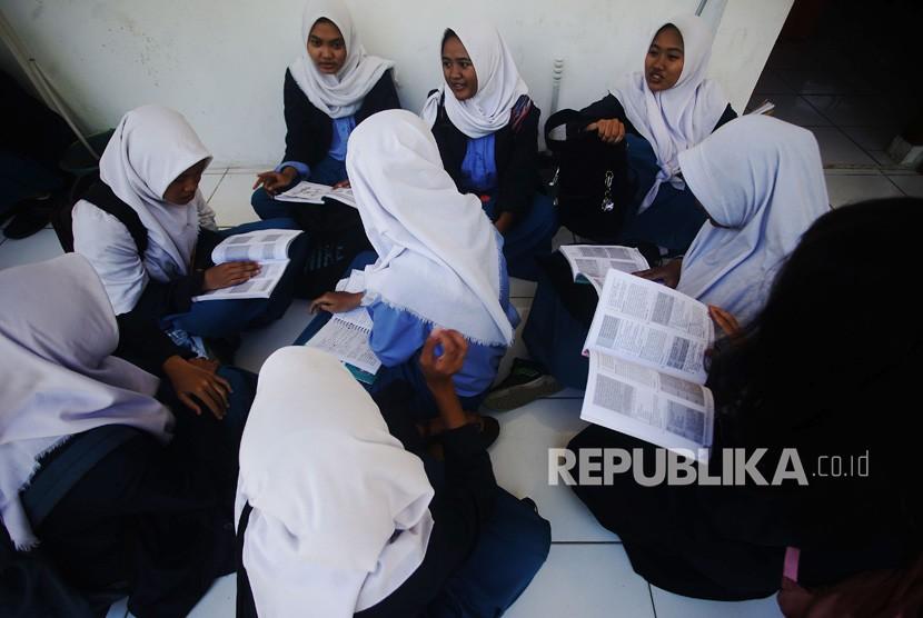 Siswa Sekolah Menegah Kejuruan Negeri (SMKN) 3 Depok mengulang pelajaran di teras kelas saat menunggu Ujian Nasional Berbasis Komputer (UNBK) sesi satu selesai di Sukmajaya Depok, Jawa Barat, Senin (25/3/19).