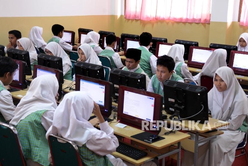 Siswa-siswi mengerjakan soal ujian mata pelajaran bahasa Indonesia saat Ujian Nasional Berbasis Komputer (UNBK)