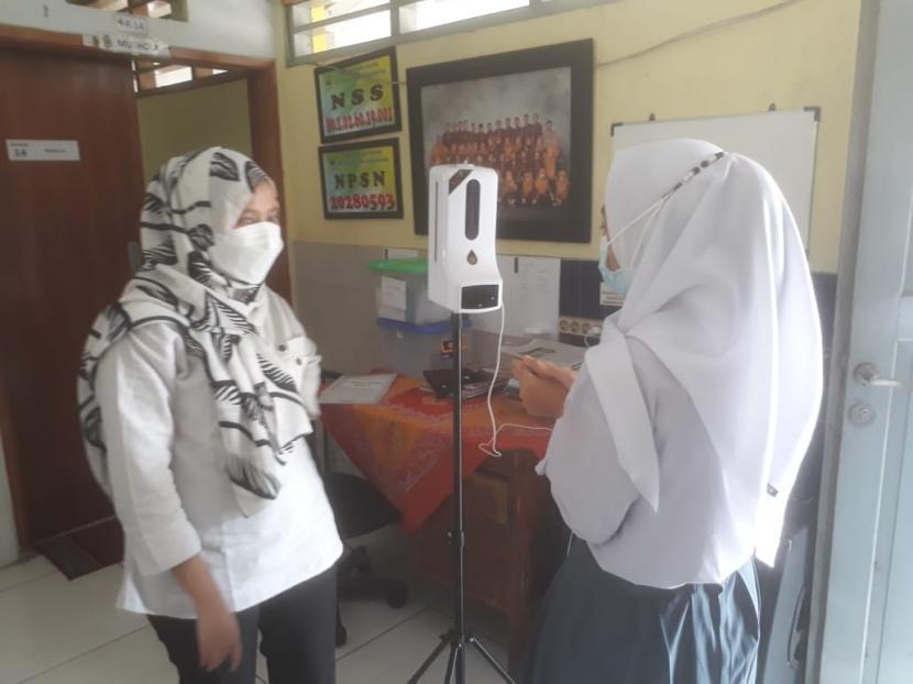 Siswa SMA SLB di Kota Bandung tengah mengecek kondisi suhu tubuh didampingi oleh petugas sekolah, Rabu (15/9).