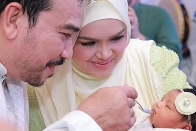 Siti Nurhaliza dan suaminya Datuk Seri Khalid Mohamad Jiwa menggendong bayi mereka.