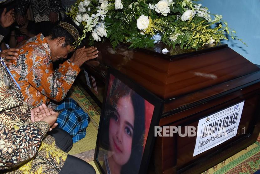 Slamet, ayah Alfiani Hidayatul Solikah, pramugari pesawat Lion Air JT 610 yang mengalami kecelakaan berdoa sambil memeluk peti jenazah Alfiani di rumah duka Desa Mojorejo, Kebonsari, Kabupaten Madiun, Jawa Timur, Rabu (14/11/2018).