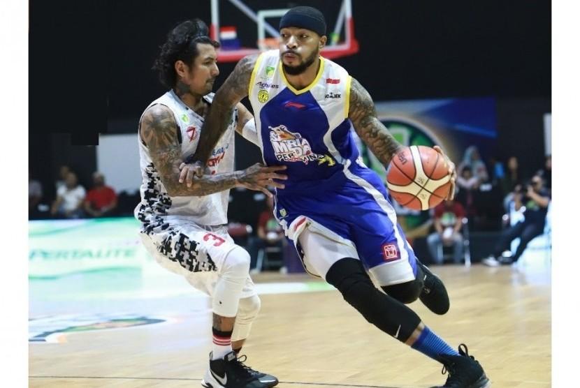 Small Forward Satria Muda Pertamina Jamarr Andre Johnson dijaga point guard Hangtuah Sumsel Kelly Purwanto.
