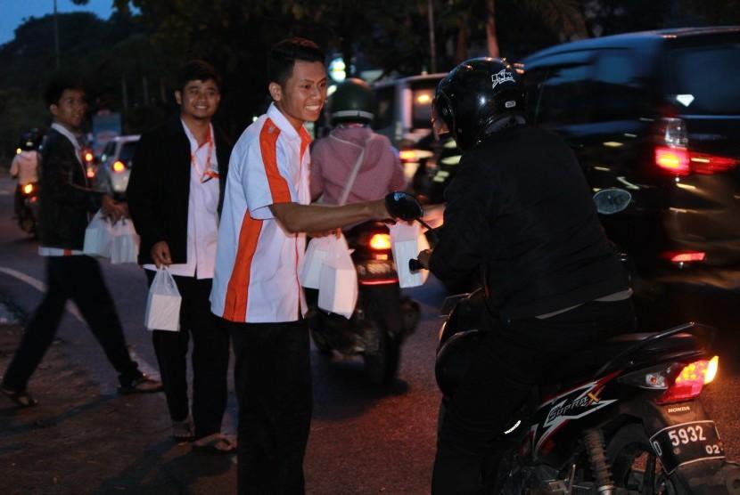Staf BMH membagikan takjil gratis di Bandung.