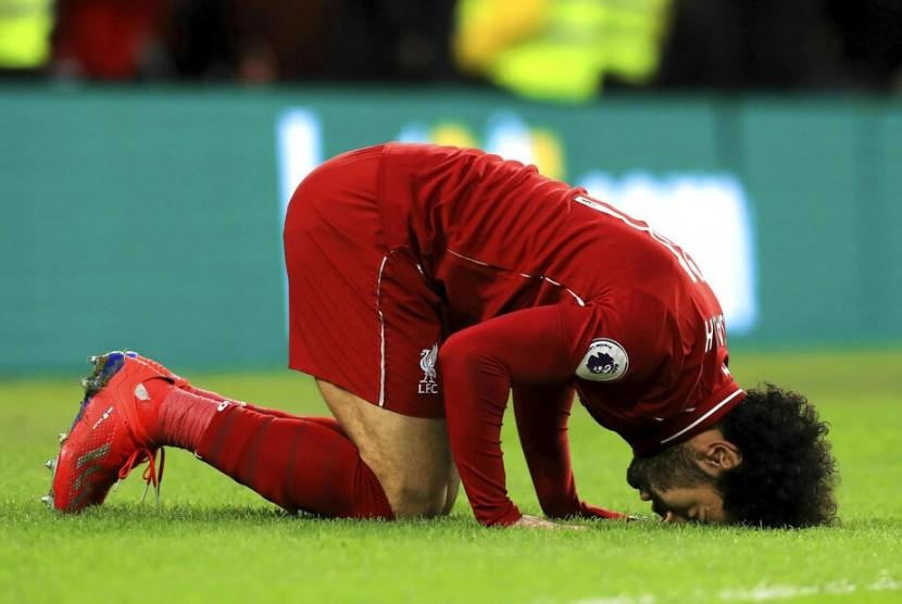Striker Liverpool, Mohamed Salah bersujud syukur setelah mencetak gol ke gawang Brighton & Hove Albion FC pada laga Liga Primer Inggris, Sabtu (13/1) malam. Liverpool menang 1-0.