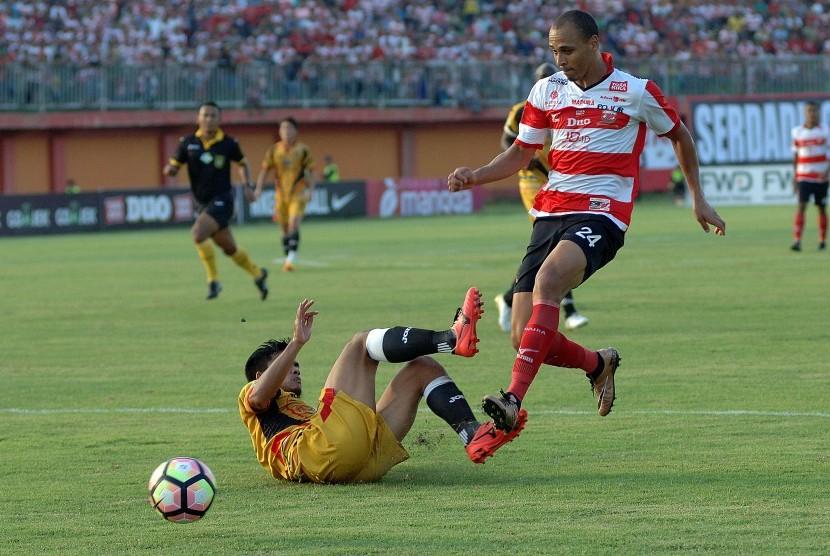 Striker Madura United (MU) FC Peter Odemwingie (kanan) melewati hadangan pesepak bola Mitra Kukukar, Dhika Pratama Putra (kiri bawah) dalam lagaLiga 1 di Stadion Gelora Ratu Pamelingan (SGRP) Pamekasan, Jumat (28/4). Melawan PS TNI, Madura United akan menggunakan Stadion Gelora Bangkalan.