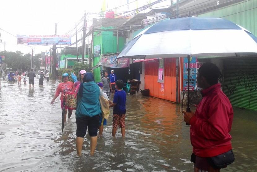 Suasana banjir di ruas Jalan Bintara Raya yang terendam air luapan Kali Cakung, Selasa (21/2).