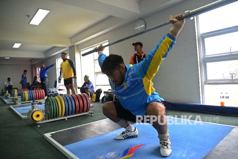 Ilustrasi atlet angkat besi melakukan pemanasan.