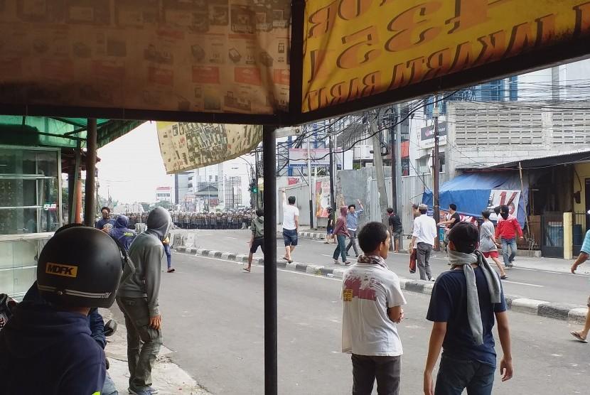 Suasana sebelum massa melempari pagar betis yang dibuat polisi di Jl Brigjen Katamso, Slipi, Jakarta Barat, Rabu (22/5) sore WIB.