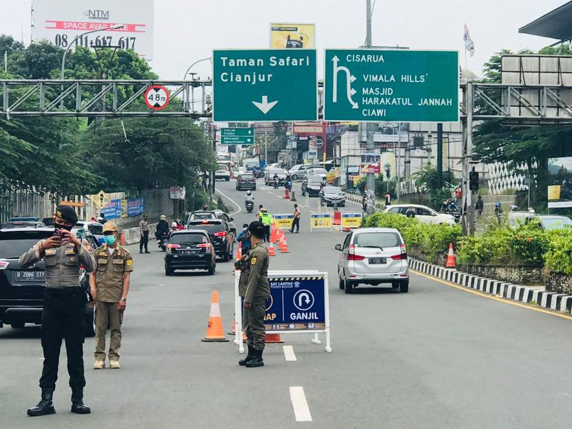 Suasana uji coba ganjil-genap kendaraan bermotor kawasan Puncak, tepatnya di Simpang Gadog, Ciawi, Kabupaten Bogor, Ahad (12/9).