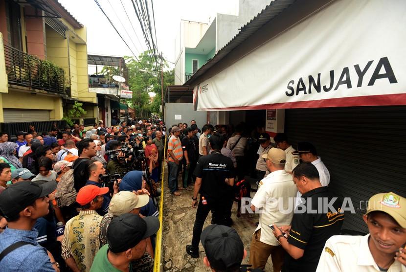 Suasana warga saat melihat lokasi pembunuhan satu keluarga di Jalan Bojong Nangka II, Jatirahayu, Pondok Melati, Bekasi, Jawa Barat, Selasa (13/11).