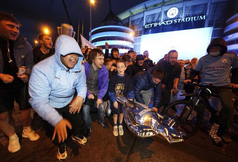 Suporter Manchester City berpesta di luar Etihad Stadium di Manchester, Inggris, Selasa 11 Mei 2021, usai tim mereka merebut gelar Liga Inggris. Man City merebut gelar setelah rival sekota Manchester United kalah di kandang dari Leicester City.